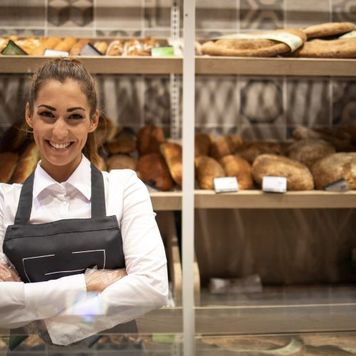 portrait-of-bakery-seller-with-arms-crossed-standing-in-front-of-shelf-full-of-bred-bagels-and-pastry