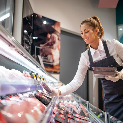 supermarket-worker-organizing-position-in-meat-department