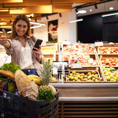 woman-with-smart-phone-in-supermarket-standing-by-the-shelves-full-of-fruit-at-grocery-store-holding-thumbs-up