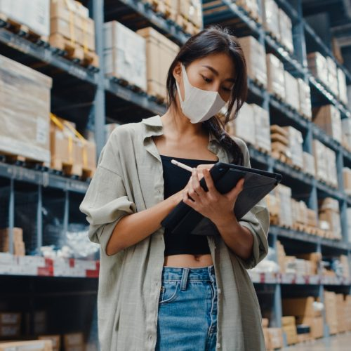 young-asian-businesswoman-manager-wearing-face-mask-warehouse-using-digital-tablet-checking-inventory
